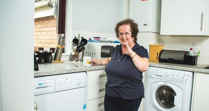 A woman laughing in her kitchen.
